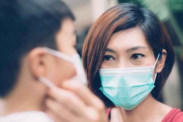 Mutter kümmern sich sohn mit gesichtsmaske für schutzkrankheit grippe oder covid-19.