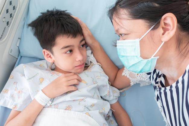 Mutter kümmert sich um ihren sohn, während er im krankenhaus krank ist