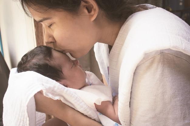 Mutter küssen stirn ihr neugeborenes, weinlese