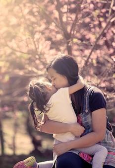 Mutter küssen und umarmen tochter im rosa blumenhintergrund im weinlesefarbfilter