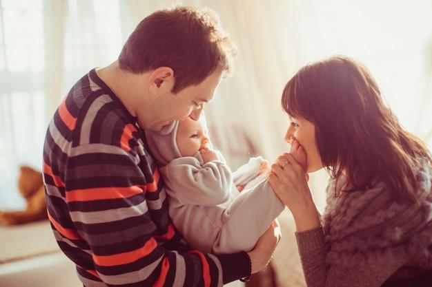 Mutter küsst die füße des kindes, während vater es hält