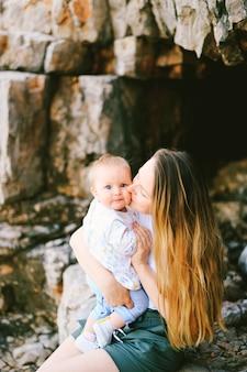 Mutter küsst ihr baby auf die wange, während sie an einem felsigen strand sitzt