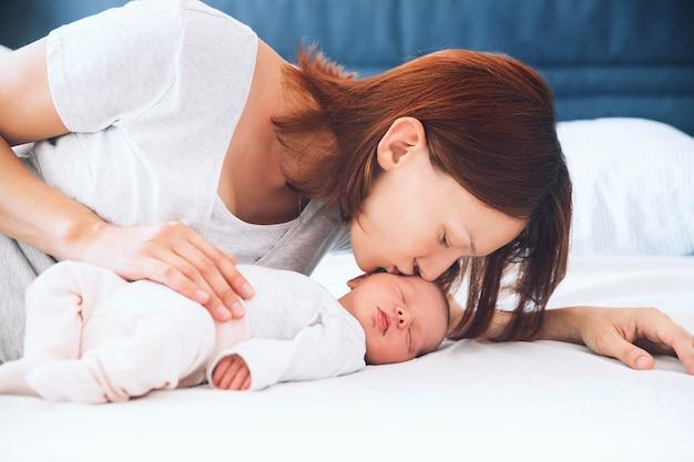Mutter küsst ihr neugeborenes baby junge schöne mutter liegt mit einem süßen kleinen schlafenden kind im bett