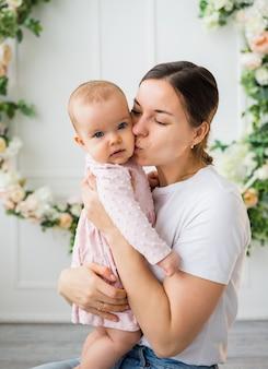 Mutter küsst kleine tochter auf weißem hintergrund mit blumen