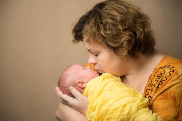 Mutter küsst neugeborenes. gelbe kleidung