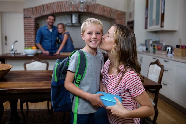 Mutter küsst seinen sohn und gibt ihm eine lunchbox