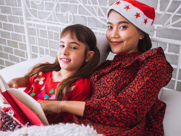 Mutter las ein buch zu ihrer tochter am weihnachtstag, glückliches familienkonzept