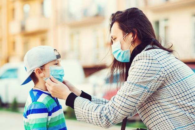 Mutter legt ihrem sohn eine gesichtsschutzmaske ins freie. stoppen sie die ausbreitung des coronavirus. schutzmaßnahmen.