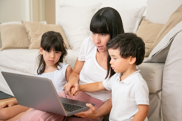 Mutter lehrt kinder, laptop zu benutzen, hand des kleinen sohnes zu halten und tastaturknopf mit jungenfinger zu drücken.