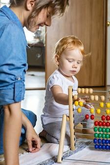 Mutter lehrt kleines kind, das auf mehrfarbigem, kindlichem ökologischem abakus aus holz auf dem boden zählt