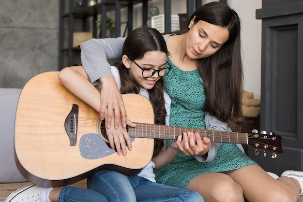 Mutter lehrt mädchen, gitarre zu spielen