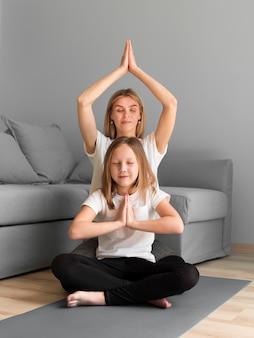 Mutter lehrt mädchen, yoga zu machen