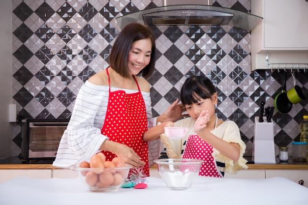 Mutter lehrt tochter teig in der küche zubereiten. konzept familie glücklich.