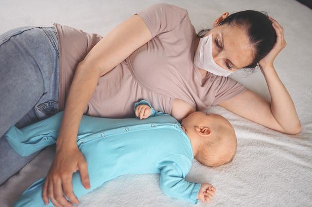 Mutter liegt mit neugeborenen baby im blauen overall umarmt und stillt ihn mit muttermilch
