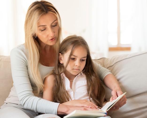 Mutter liest buch zu tochter zu hause