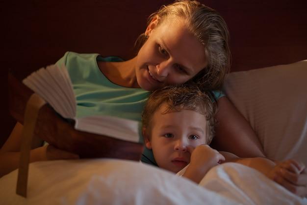 Mutter liest ihrem kleinen sohn eine gutenachtgeschichte vor