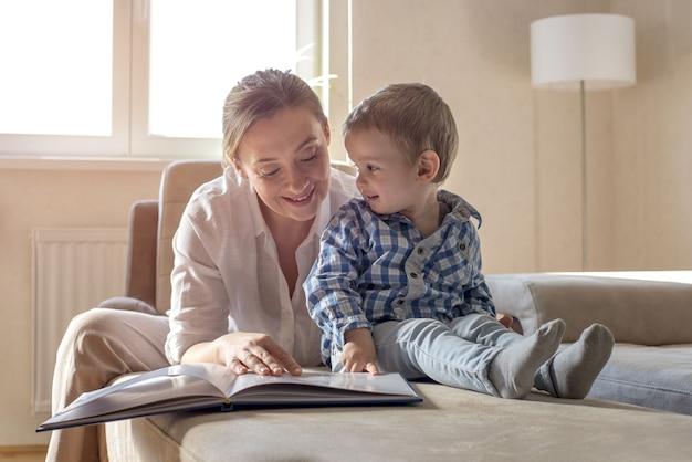Mutter liest ihrem kleinen sohn zu hause ein buch vor