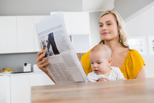 Mutter liest zeitung mit baby in der küche