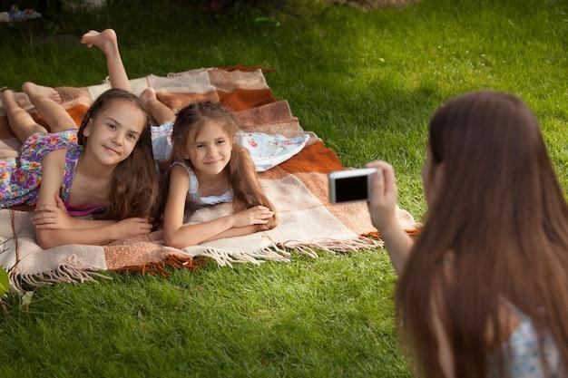 Mutter macht foto von zwei kleinen mädchen, die auf gras liegen