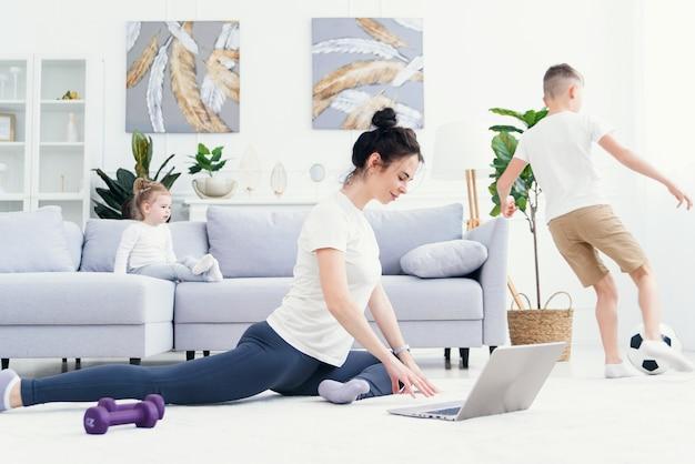 Mutter meditiert mit tochter, während aktiver energetischer kindersohn spielt, mutter arbeitet und macht yoga-übung zu hause für stressabbau, der sich mit ungezogenem kleinen kind entspannt. 4k videoaufnahmen zeitlupe