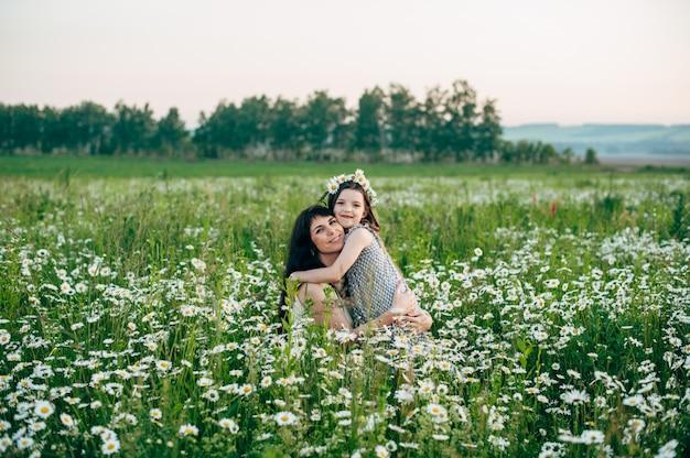 Mutter mit baby auf dem gänseblümchengebiet bei sonnenuntergang. tonen