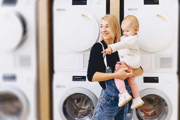 Mutter mit baby auf dem hintergrund von waschmaschinen