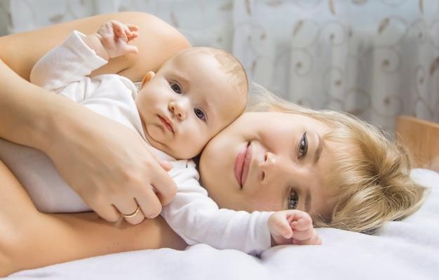 Mutter mit baby auf einem hellen hintergrund. selektiver fokus. menschen.