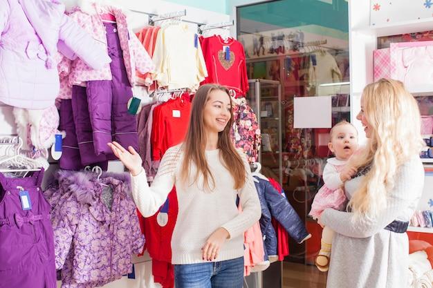 Mutter mit baby besucht den bekleidungsladen mit winterkleidung