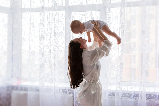 Mutter mit baby in der nähe des schlafzimmerfensters