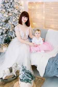 Mutter mit baby, kleider tragend, auf sofa auf dem hintergrund des weihnachtsbaumes sitzend
