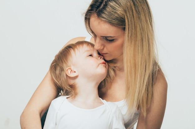 Mutter mit babyporträtkind frau mit blonden haaren und tochterkuss
