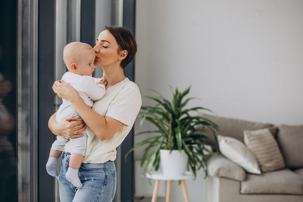 Mutter mit babysohn steht zu hause am fenster