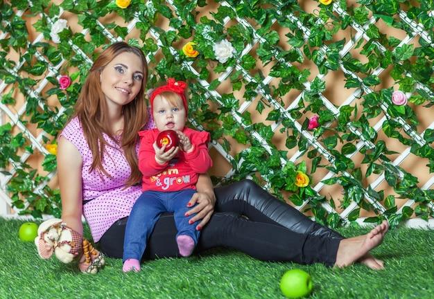 Mutter mit dem baby an hand, das auf dem gras im blumengarten sitzt