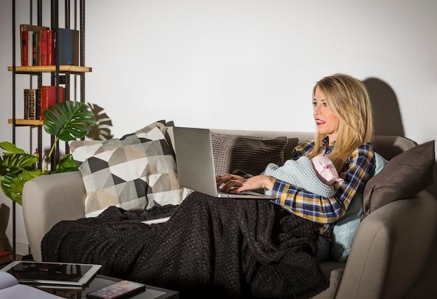 Mutter mit dem baby, das laptop auf couch verwendet