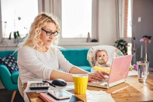 Mutter mit dem baby, das zu hause büro des laptops verwendet