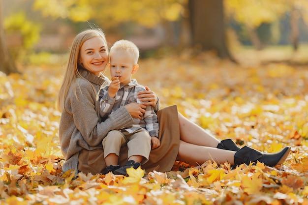 Mutter mit dem kleinen sohn, der auf einem herbstgebiet sitzt