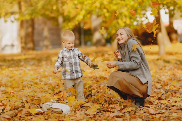 Mutter mit dem kleinen sohn, der auf einem herbstgebiet spielt