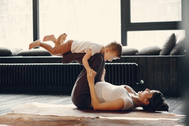 Mutter mit dem kleinen sohn, der zu hause yoga tut