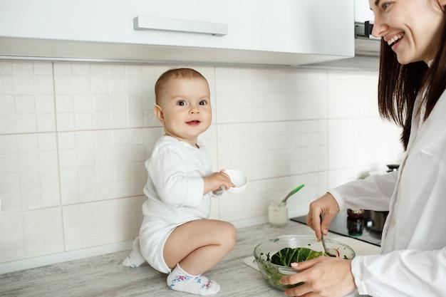 Mutter mit dem niedlichen baby, das in der küche kocht