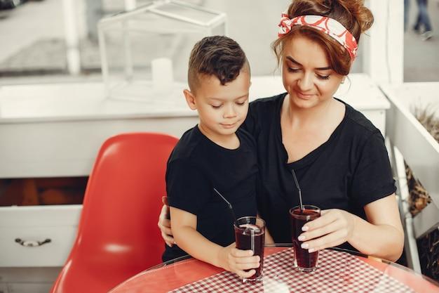 Mutter mit dem sohn, der in einem café sitzt
