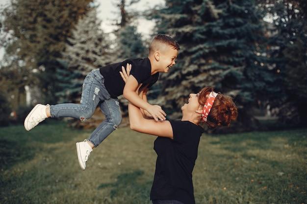 Mutter mit dem sohn, der in einem sommerpark spielt