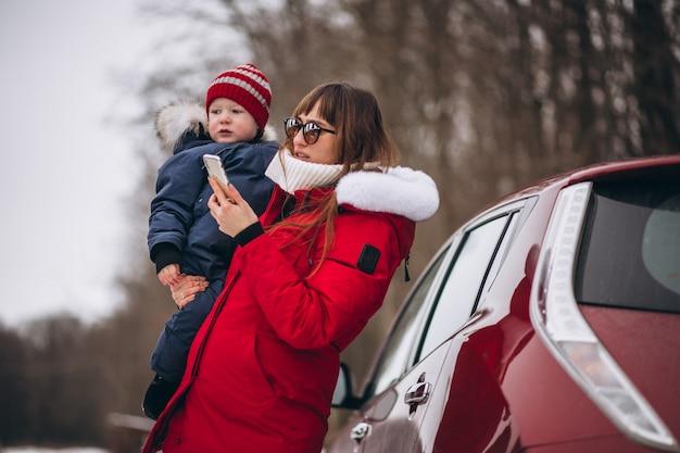 Mutter mit dem sohn, der mit dem auto steht