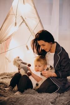 Mutter mit dem sohn, der zu hause im gemütlichen zelt mit lichtern auf weihnachten sitzt