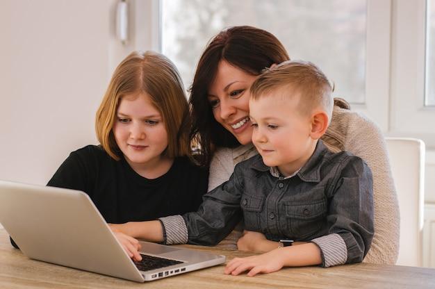 Mutter mit den kindern, die zu hause karikaturen auf computer aufpassen