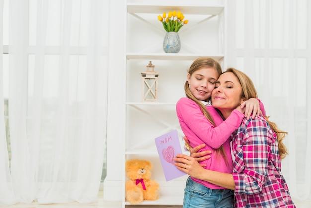 Mutter mit der grußkarte, die tochter umarmt