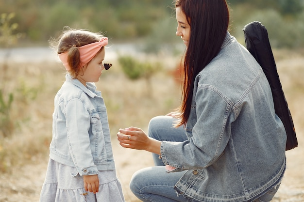 Mutter mit der kleinen tochter, die auf einem gebiet spielt