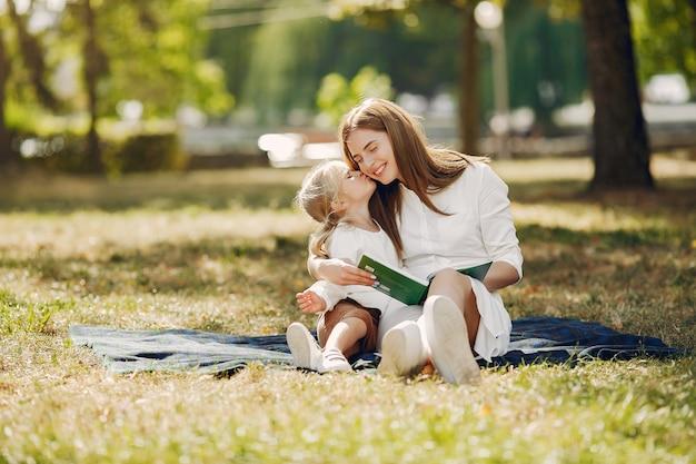 Mutter mit der kleinen tochter, die auf einem plaid sitzt und das buch liest