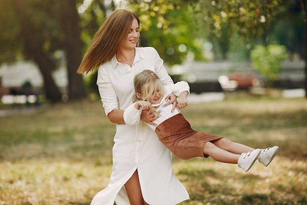 Mutter mit der kleinen tochter, die in einem sommerpark spielt