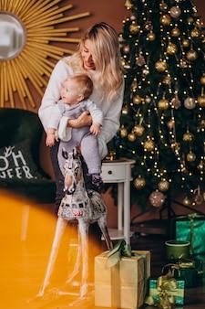 Mutter mit der netten tochter, die auf einem hölzernen pony durch weihnachtsbaum sitzt