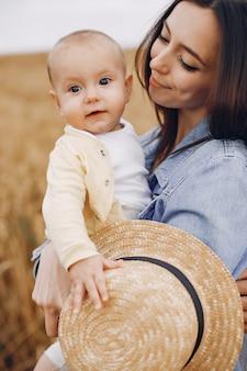 Mutter mit der tochter, die auf einem herbstgebiet spielt